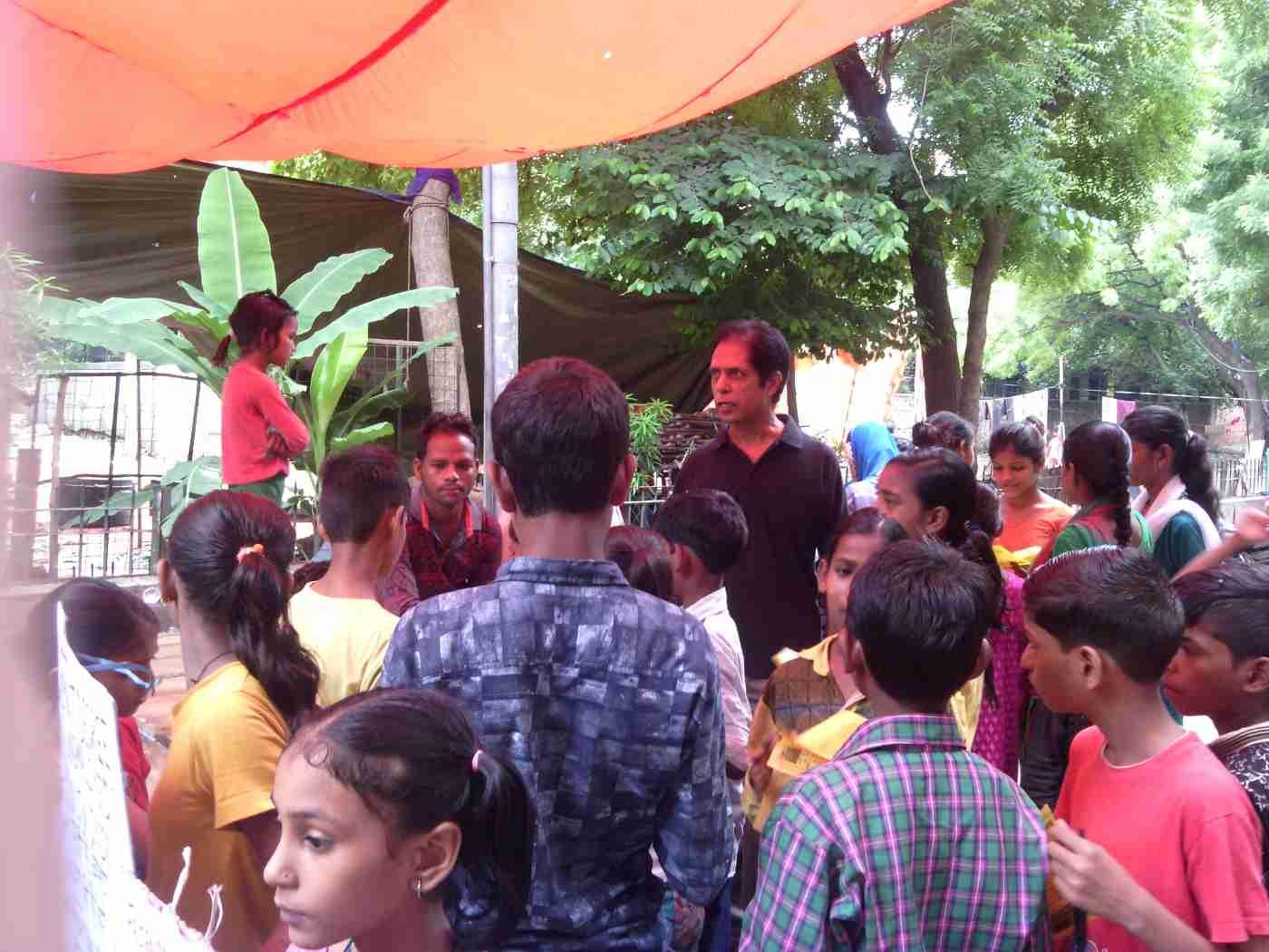 RMN Foundation School teacher Rakesh Raman explaining the benefits of modern alternative education to people in a street of Delhi.